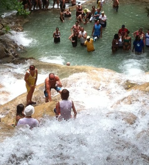 People sitting in water at Dunn's River Falls
